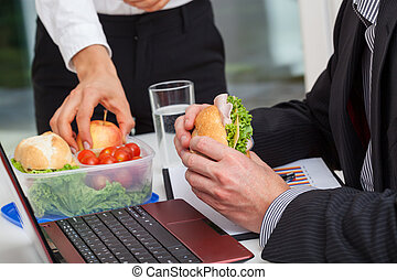Healthy lunch at the desk - Managers with healthy lunch at...