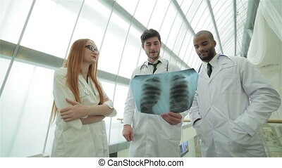 Three confident doctor examining x-ray snapshot of lungs