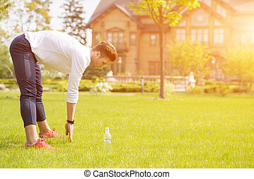 Healthy male athlete doing exercise in nature
