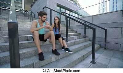 Healthy man and woman having a rest after morning training, sitting and talking on stairs at modern stadium