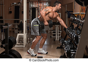 Healthy Man Doing Exercise For Back With Dumbbells