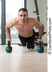 Healthy Man Doing Push-ups On Floor With Kettle-bell