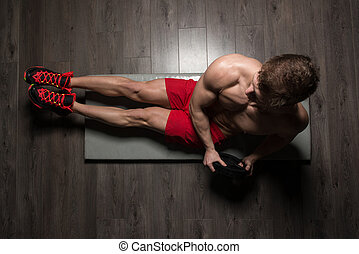 Healthy Man Doing Sit-Ups On Foor With Weights