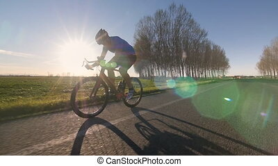 healthy man racing on bike - cyclist rides bike working out...