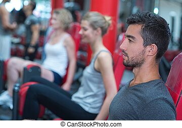 healthy man training in gym with people