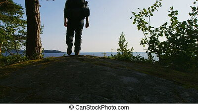 Healthy man with large backpack walks on the mountain by the sea at sunset