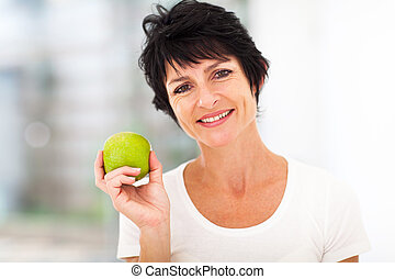 healthy mid age woman holding apple