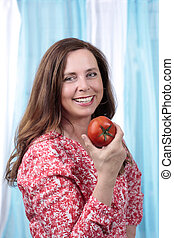 Healthy middle age woman with tomato