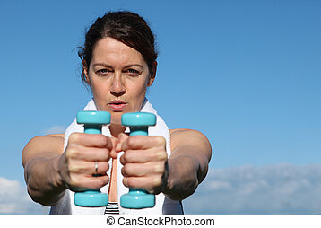 healthy middle aged woman exercising with weights