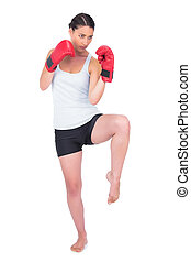 Healthy model with boxing gloves kicking while posing on...