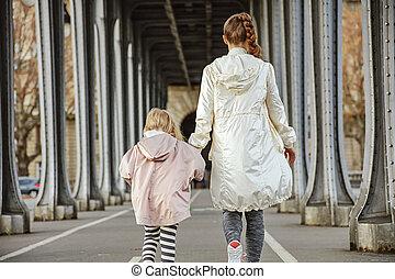 healthy mother and child on Pont de Bir-Hakeim bridge walking