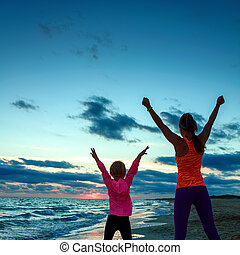 healthy mother and daughter on seacoast on sunset rejoicing