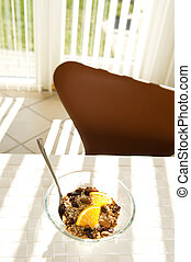 Healthy muesli with orange in the morning sun