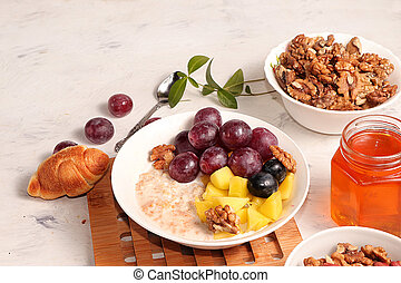 Healthy natural breakfast, food for children. Oatmeal with grapes, nuts and honey, selective focus. Healthy eating concept.