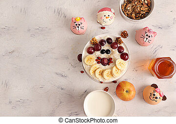 Healthy natural breakfast, funny food for children. Oatmeal with grapes, nuts and honey, top view, selective focus. Healthy eating concept.