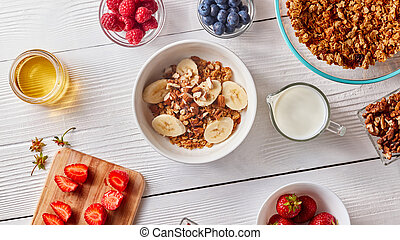 Healthy natural breakfast with organic ingredients corn flakes, banana slices in white bowl and milk, berries, honey, nuts on white.
