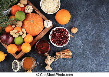 Healthy natural food for the flu and colds. Selection of fresh fruits and vegetables with vitamin C, tangerines, cabbage, cranberries, cinnamon, honey on a concrete table.