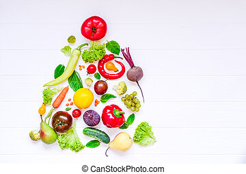 Healthy new year concept - fresh organic vegetables, herbs and fruits in the form of christmas tree on white wooden background. Diet, detox planning. Top view. Selective focus. space for text.