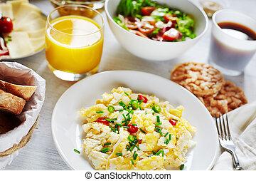 Fresh breakfast food. Scrambled eggs, salad, coffee and orange juice. Cocept of healthy food or continental breakfast.