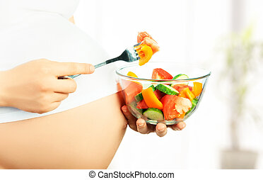 healthy nutrition and pregnancy. pregnant woman's belly and vegetable salad