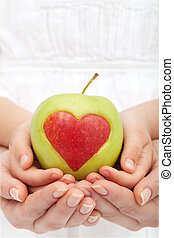 Healthy nutrition concept - hands holding apple with heart cutout