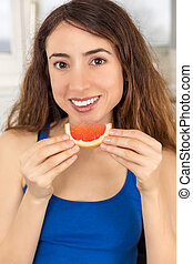 Healthy nutrition woman eating grapefruit