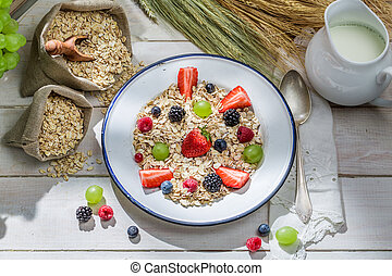 Healthy oat flakes with fresh fruits for breakfast