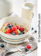 Healthy oat flakes with fruits for breakfast on rustic table