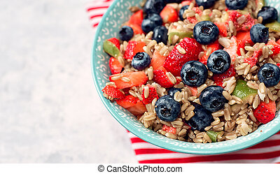 healthy oatmeal with fruits and berries, strawberries, blueberries and figs in a blue bowl on a gray background for Breakfast