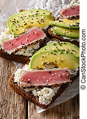 Healthy open sandwiches with fried tuna in sesame, avocado and cream cheese close-up. vertical