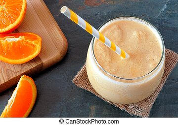 Healthy orange smoothie in a glass with striped straw and fresh fruit slices, downward view on slate