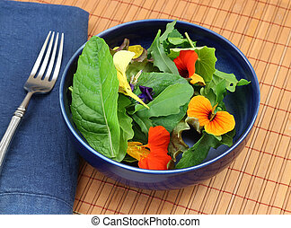 Healthy fresh organic green salad with edible flowers (nasturtiums, violets).