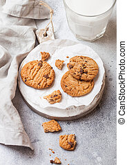 Healthy organic oat cookies with chocolate with glass of milk on wooden board on stone kitchen table background.