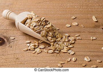 oat flakes on wooden table with scoop