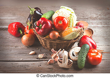 Healthy organic vegetables in basket on wooden background