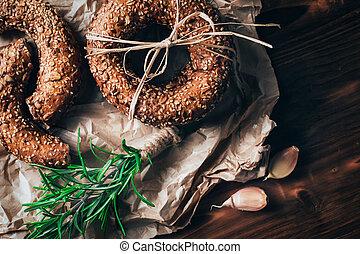 Healthy organic whole grain bagel on wooden table. Breakfast bread.