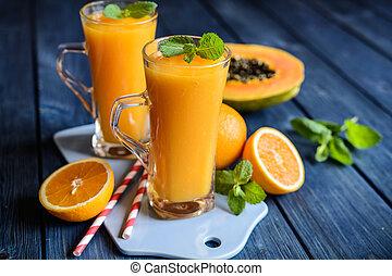 Healthy papaya, orange and mango smoothie in a glass jar