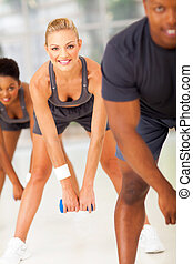 people in a row doing fitness exercise with dumbbell