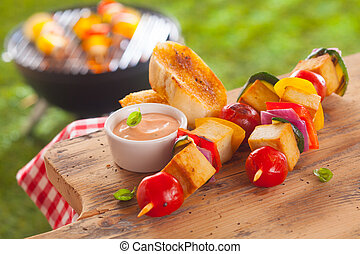 Healthy picnic lunch at a summer barbecue with grilled smoked Tofu and vegetable kebabs served with a savory sauce and toasted baguette on a wooden table