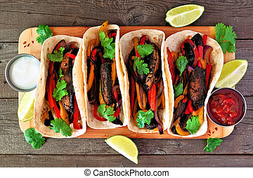 Portobello mushroom vegan fajitas. Top view on a wood background. Healthy eating, plant-based meat substitute concept.