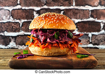 Healthy, plant based meatless pulled carrot burger against a...