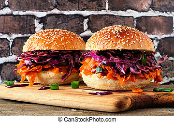 Pulled carrot meatless burgers with red cabbage slaw against a dark brick background. Healthy eating, plant-based meat substitute concept.