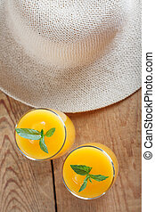 Healthy pumpkin fruit smoothie with straw hat on vintage wood background