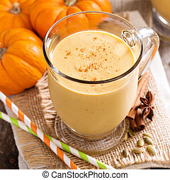 Healthy pumpkin smoothie in big mugs on rustic background