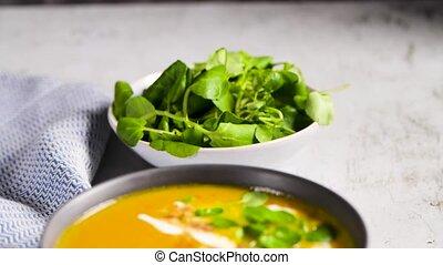 Healthy Pumpkin soup with cream and organic pumpkin seeds.