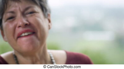 Healthy retired woman in her 60s laughing out loud and...
