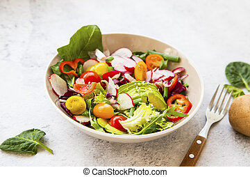 Healthy salad bowl with fresh vegetables, avocado, tomatoes, pepper, radishes, green arugula, onion, spinach and lettuce in a bowl with olive oil and hemp seeds