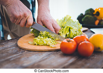 Close up of lettuce being cut on the cutting board