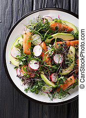 Healthy salad of salmon, avocado, radish and microgreen mix close-up on a plate. Vertical top view