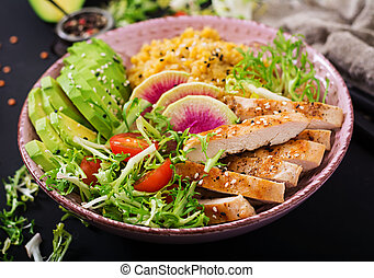 Healthy salad with chicken, tomatoes,  avocado, lettuce, watermelon radish and lentil on dark background.